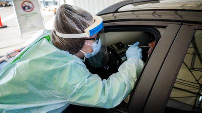 En vårdare i skyddsutrustning tar ett coronatest på en person som sitter i en bil.