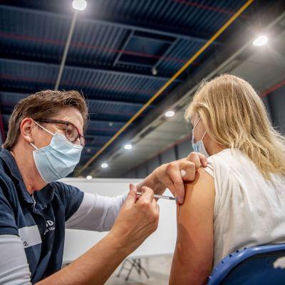 En blond ung person sitter på en stol. En vårdare böjer sig ner bredvid henne och ger en spruta i armen. Vårdaren bär munskydd.