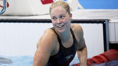 Fanny Teijonsalo i svart simdräkt och utan badmössa kommer upp ur bassängen.