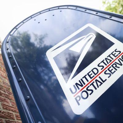 Yhdysvaltalainen postilaatikko komeilee sinisenä tiiliseinän edessä.