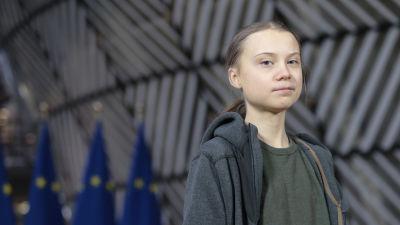 Greta Thunberg står framför Europeiska Unionens flaggor.