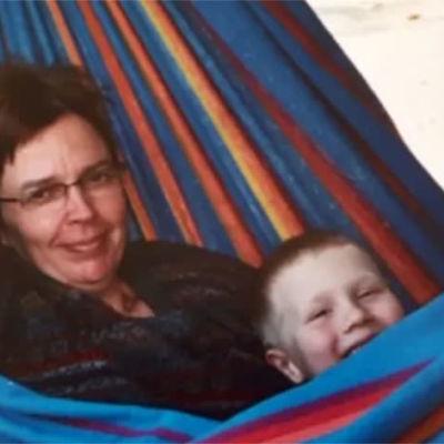 Äiti ja lapsi lepäävät riippukeinussa.