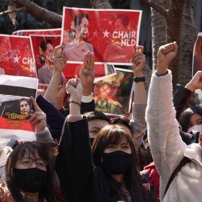 Människor i svarta munskydd håller sina händer i luften. De knyter sina nävar eller håller upp plakat.