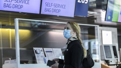En kvinna med ansiktsskydd och Finnairs uniform står framför en check-in-disk.