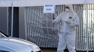 En person i skyddsutrustning går mot en bil för att genomföra ett drive-in coronatest i Landsberg i Tyskland.