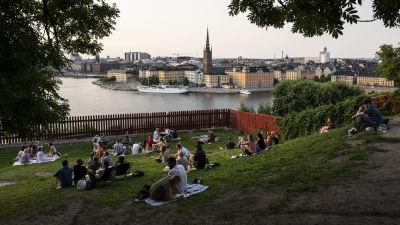 Människor sitter i Ivar Los Park i Stockholm. En vy över staden syns vid vattnet.
