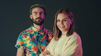 axel står till vänster med färgrann skjorta på sig och keps. hanna står till höger i ljusgul collegetröja.