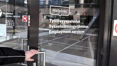 En person med handen på dörrhandtaget vid Arbets- och näringsbyrån i Helsingfors.