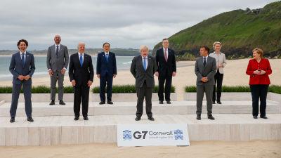 Sju män och två kvinnor poserar på en sandstrand.