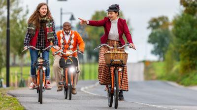 Två kvinnor och en man cyklar på en asfalterad väg. De ser glada ut.