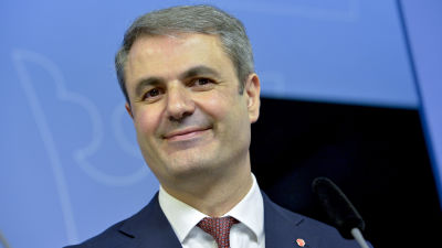 En leende man i medelåldern med mörkt hår och mörka ögon tittar in kameran. Han är klädd i röd kravatt och blå kostym. Han ler utan att tänderna syns.