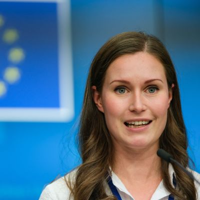 Sanna Marin med EU:s flagga i bakgrunden
