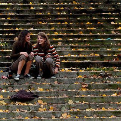 Kaksi tyttöä istuu portailla.