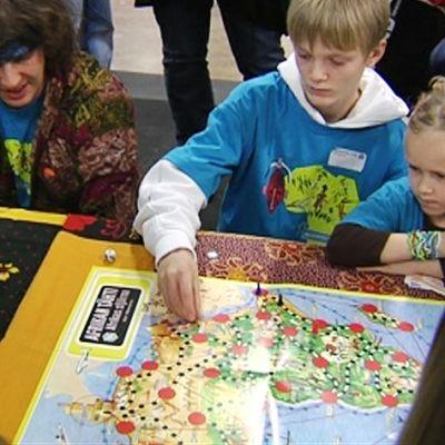 Lapsia ja aikuisia pöydälle levitetyn Afrikan tähti -pelin ympärillä.