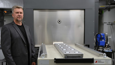 Man i grå kostym står bredvid en krematoriugn.