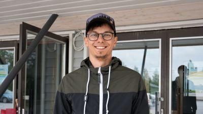 Ung man i keps och glasögon står framför en vit byggnad.