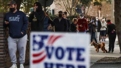 """Människor står i kö på en gata med en """"vote here"""" skylt i förgrunden."""