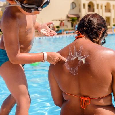 Ett barn som smörjar en kvinnas rygg.