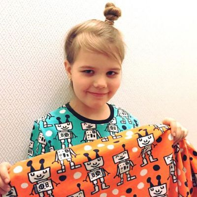 Kuvassa tyttö näyttää käsissään olevaa kangasta, jossa on robotin kuvia.