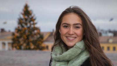 Porträttbild på Finlands lucia framför en julgran.