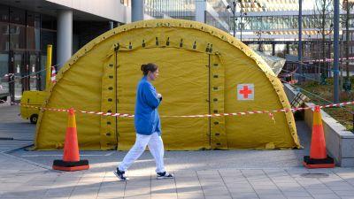 En sjukskötare går utanför ett gult tält.
