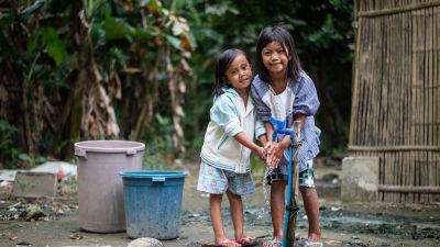 två filippinska flickor tvättar händerna vid en vattenpost