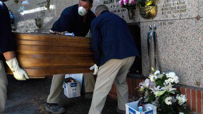 Bårhusarbetare bär på en kista.