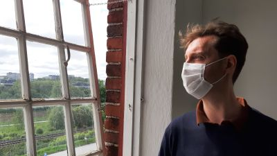 André Peterdi, en man med vitt munskydd och blå tröja, står vid ett fönster med många små rutor och tittar ut på ett sommargrönt landskap.