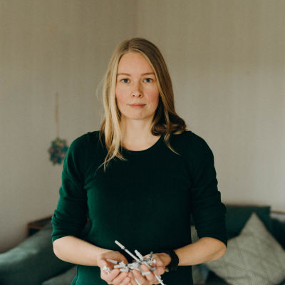 Hanna ser rakt in i kameran med händerna fulla med sprutor som hon håller framför sig.