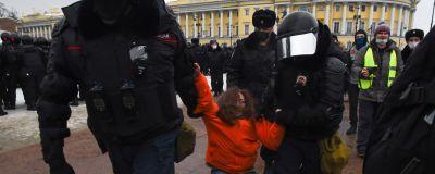 Polisen för bort en demonstrant i St. Petersburg. Den kvinnliga demonstranten strätar emot.