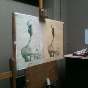 Ateljeetilassa maalaustelineessä on vieretysten kaksi hiilipiirustusta, joissa on alastoman naisen selkä.