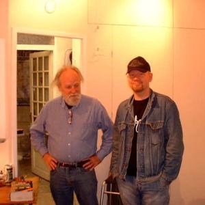 Kaksi miestä poseeraa työhuoneella. Miesten takana on pöytä, jossa on piirustustarvikkeita.