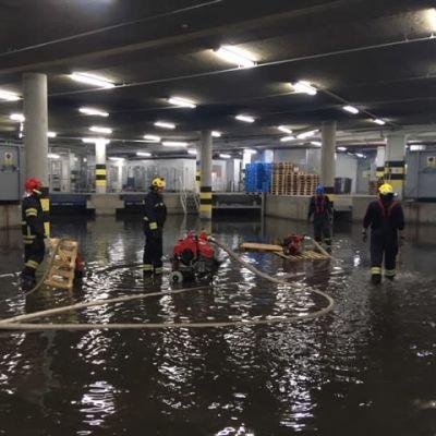 pelastajia pumppaamassa vettä kauppakeskus pasaatin kellarikerroksesta, lattialla vettä