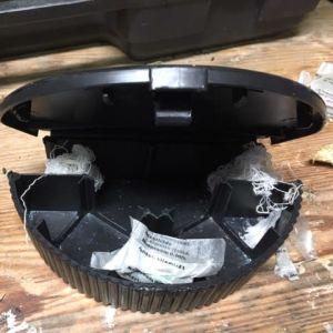 En svart musfälla i plast som är uppriven