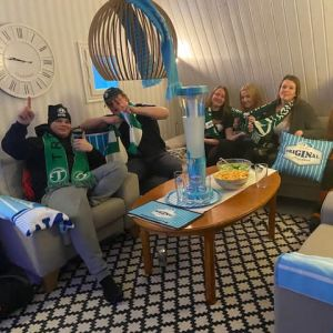 Ett kompisgäng på sex personer, kvinnor och män, sitter i två soffor. De har gröna halsdukar och bra stämning.