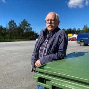 Henry Nygård står lutad mot en grön soptunna.