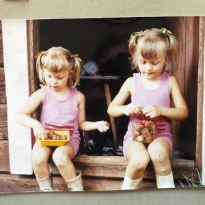 Nanna Susi ja sisko Nina aitan ovella mansikoita perkaamassa.