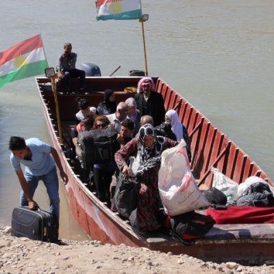 Syriska flyktingar tar i land vid en strand i Irak