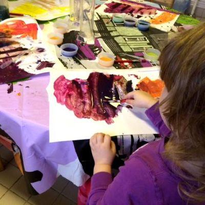 Lapsi maalaa vesiväreillä kirkkaita värejä