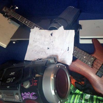 mankka, bassokitara, pelikonsoli ja niiden päällä A4-lappu