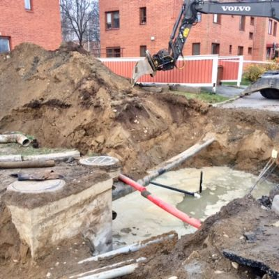 Kaivinkone kaivaa maata, kuvassa näkyy myös putkia.