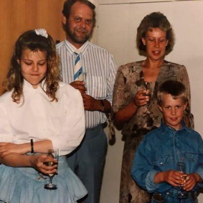 Anette med sin mamma, pappa och lillebror. Alla är festklädda och har ett champagneglas i handen.
