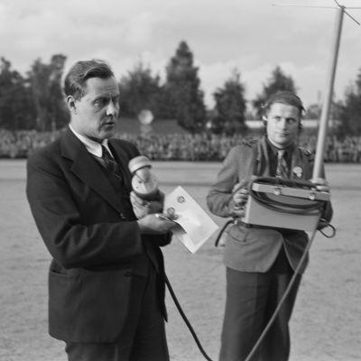 Martti Jukola selostaa urheilutapahtumaa radioon. Vieressä mies, jolla sylissään radiolähetin ja lähetinantenni.