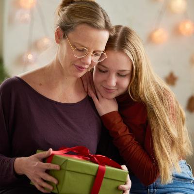 Äiti ja teini-ikäinen tyttö katsovat lahjapakettia.