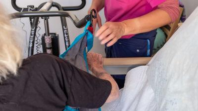 En äldre person flyttas från säng till stol med hjälp av hjälpmedel, en slags lyftanordning.
