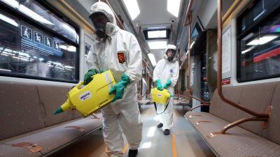 Arbetare i smittskyddsdräkter decinfiserar en metrovagn i Moskva.