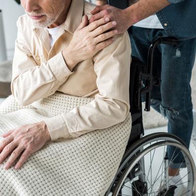 En äldre person i rullstol. Bakom honom står en man som håller en hand på hans axel.