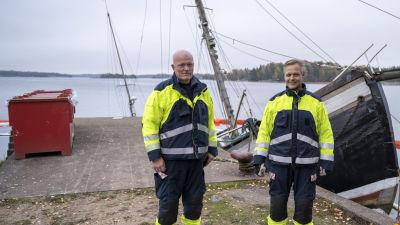 Jörgen Engroos och Fredrik Kevin står på kajen bredvid en stor trålare som ligger halvvägs under vattenytan.