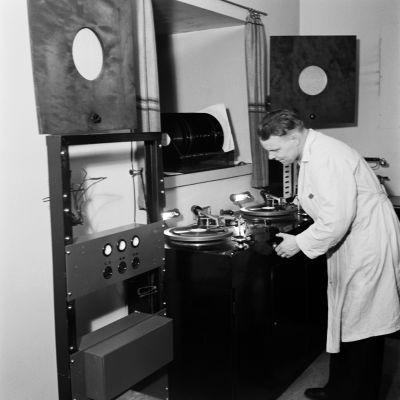 Teknikko S. Salo käyttää pikalevykaiverrinta radion äänityshuoneessa.