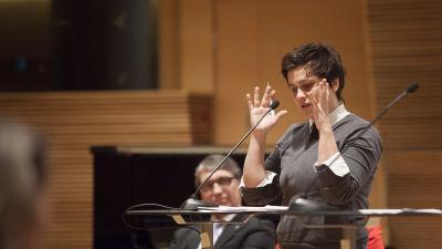 Silvia Modig står vid ett podium och gestikulerar i riksdagen.